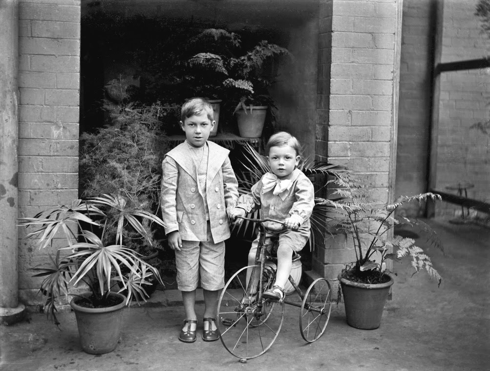 Two small boys, one on tricycle, ca. 1900.jpg